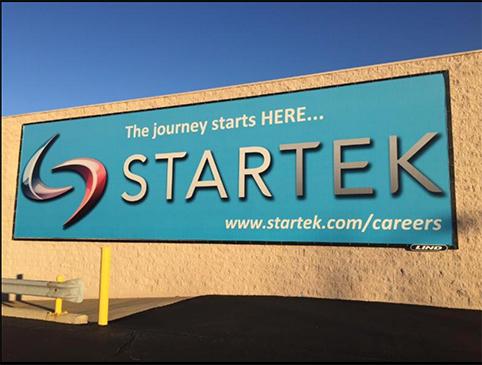Startek banner on the side of a brick building
