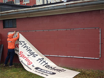 Someone attaching an outdoor banner to a Lind SignSpring installation system