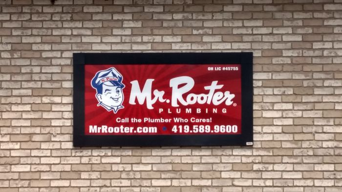 Mr. Rooter plumbing banner on a brick wall